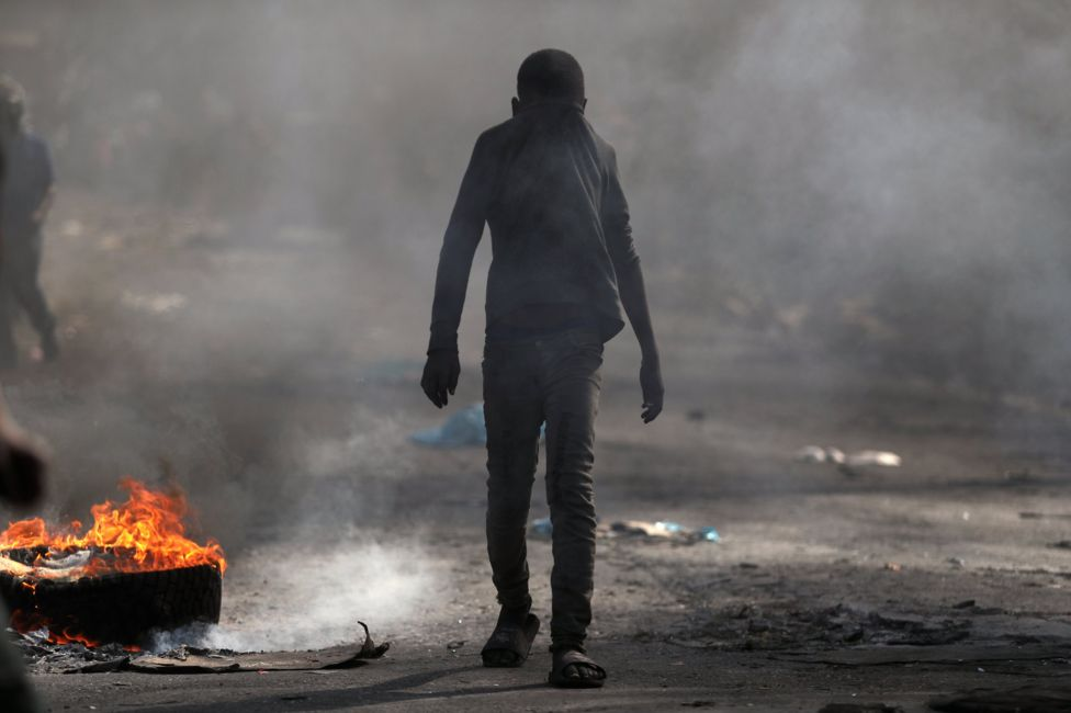 A child covers his face as he walks past a burning barricade during anti-government protests in Port-au-Prince