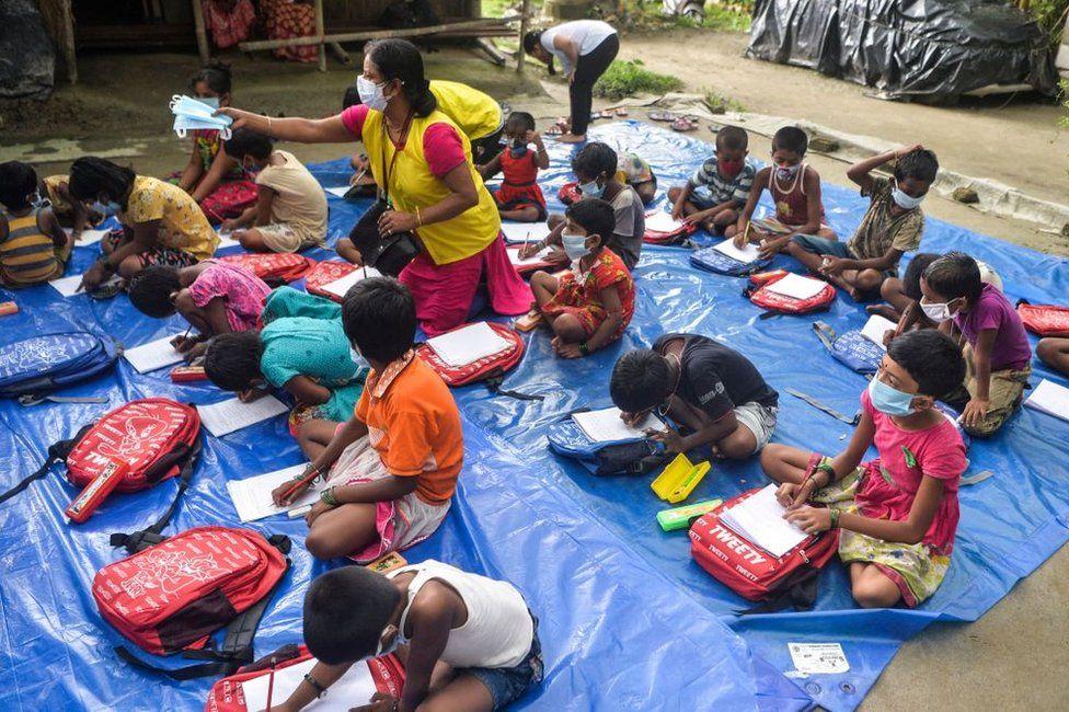 Children of a low-income neighbourhood attend open-air classes.