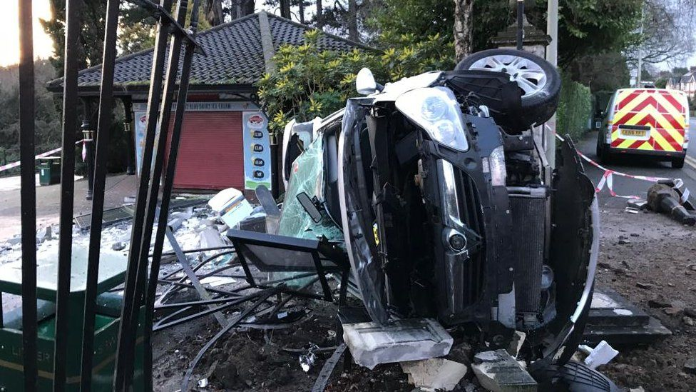 Car on its side at damaged park entrance