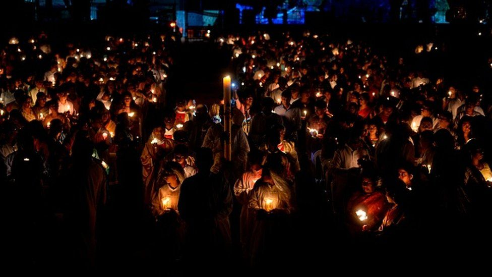 Worshippers lit candles at a midnight Easter Vigil Mass in Secunderabad, India