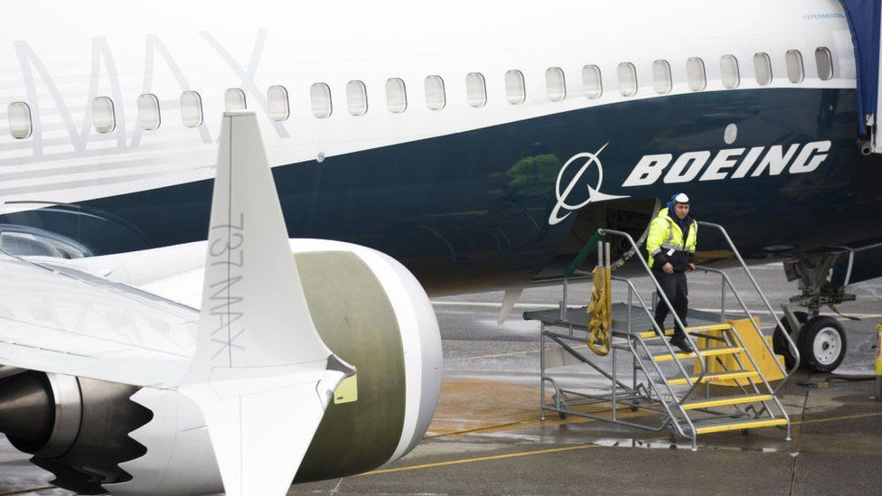 A worker stands by a Boeing 737 MAX aeroplane on the tarmac at the Boeing Renton Factory in Washington