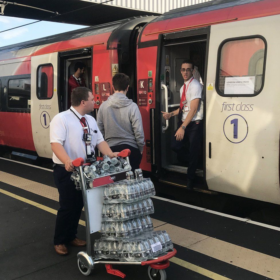 A LNER staff member pushes a trolley of bottled water at Peterborough station, as passengers wait for news during travel disruption on the East Coast mainline, after a large power cut