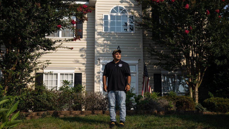 Zia Ghafoori stands in front of his home in North Carolina