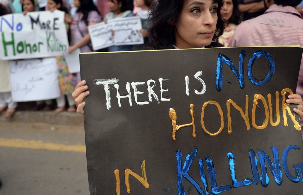 "A woman carries a sign at a 2014 protest reading: ""There is no honour in killing"""