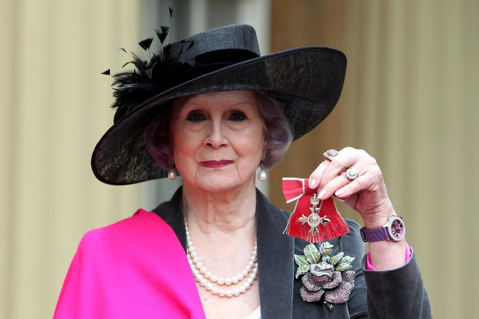 April Ashley poses with her Member of the British Empire (MBE) medal at Buckingham Palace in central London on December 13, 2012