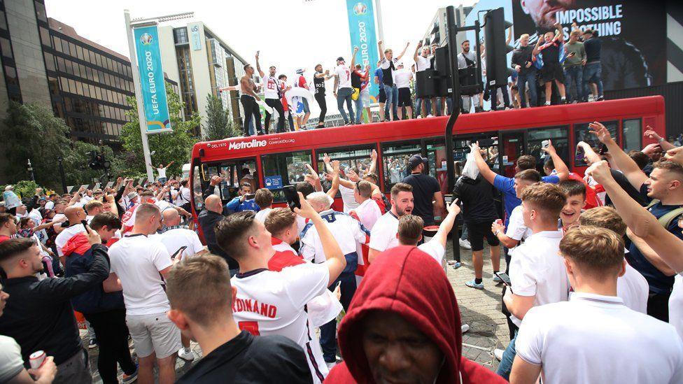 Fans climb on a bus near Wembley stadium
