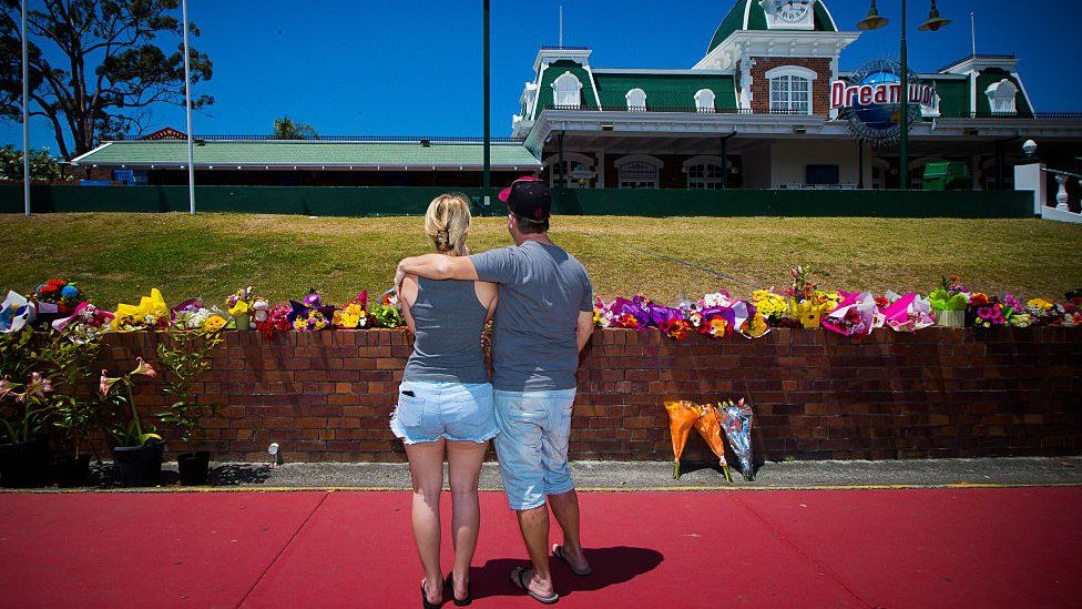 A couple stand in front of flowers outside Dreamworld after the accident in 2016