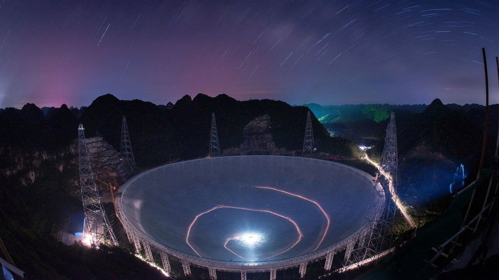 """A vehicle leaves light trails in a long exposure photo as it drives beneath the Five-hundred-meter Aperture Spherical Telescope (FAST) in Pingtang County in southwestern China""""s Guizhou Province Monday, June 27, 2016."""