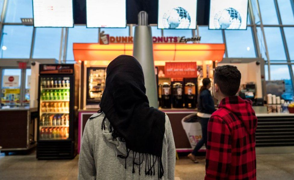 A young woman in a Hijab watches the arrivals board at New York's JFK airport