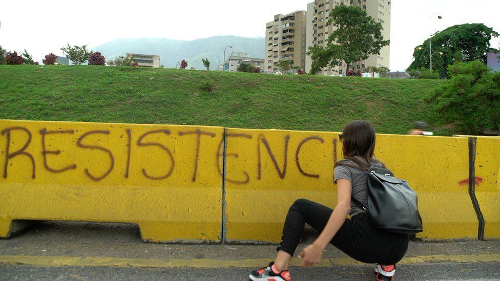 """A woman hides behind barricade with the word """"resistance"""""""