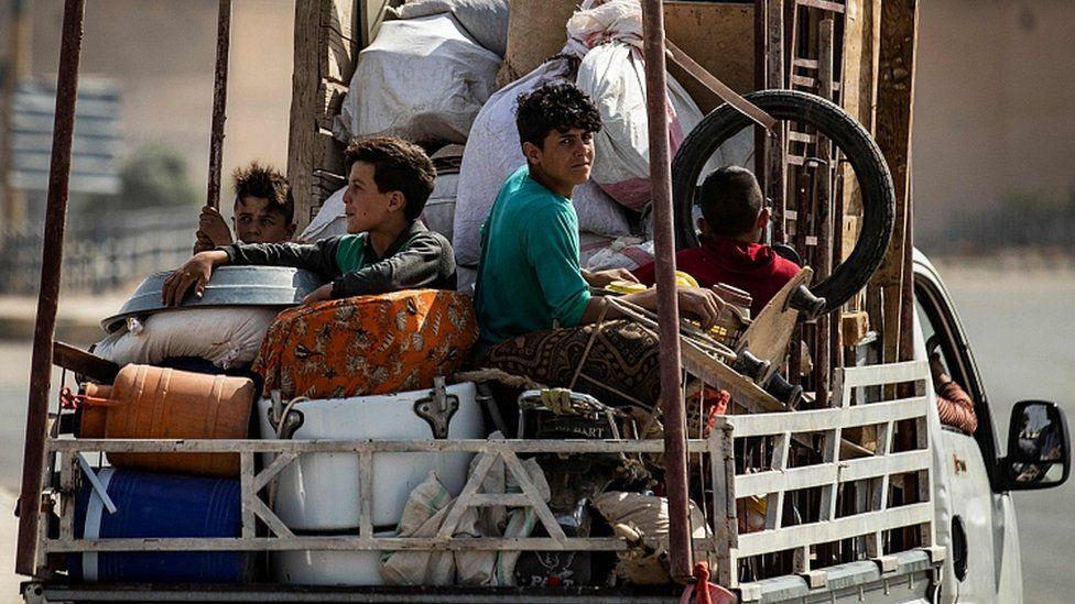 Displaced Syrians sit in the back of a truck as Arab and Kurdish civilians flee amid Turkey's military assault on Kurdish-controlled areas in north-eastern Syria, on October 11, 2019 in the Syrian border town of Tal Abyad