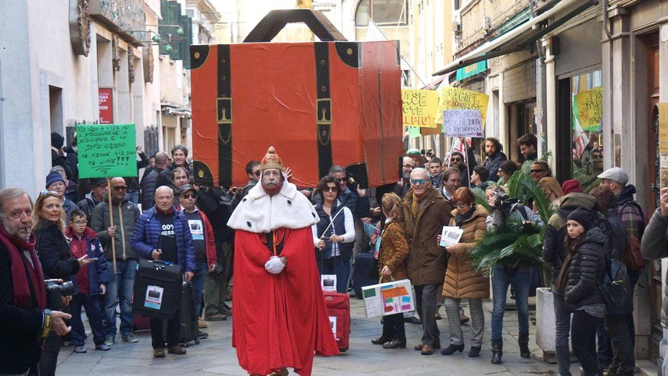 """A resident dressed like the Doge of Venice walks in front of a giant luggage during the """"Venexodus"""" demonstration."""