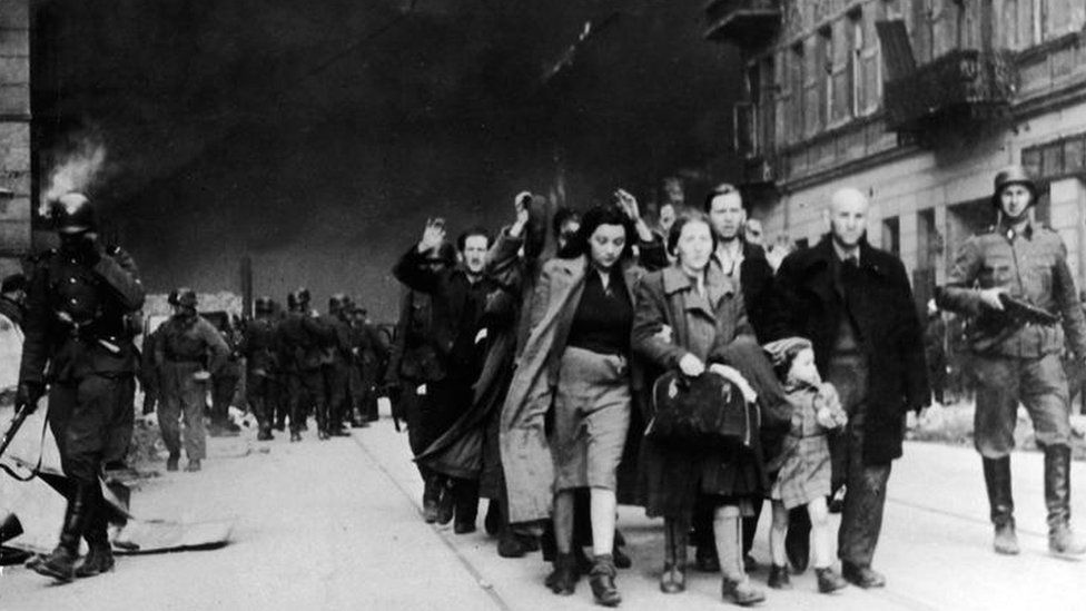 Nazi soldiers march Jews out of the ghetto on 19 April 1943