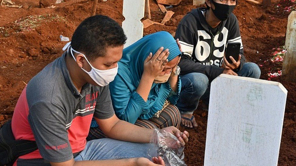 Relatives pray for a loved one during a funeral for victims of Covid-19 in Jakarta, Indonesia