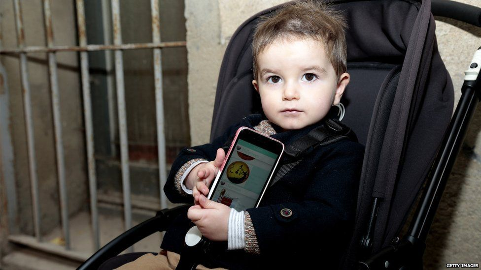 A child in a pram with a smartphone