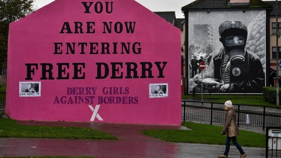 """A woman walks past a mural that states """"Derry Girls Against Borders"""" at Free Derry Corner on October 9, 2018 in Londonderry, Northern Ireland."""
