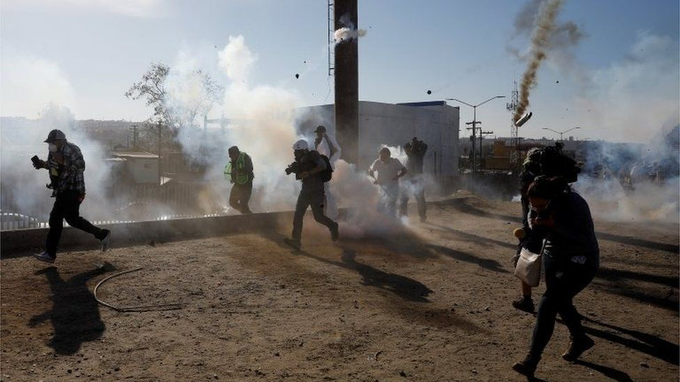 Migrants and journalists flee tear gas released by US border patrol near the fence between Mexico and the United States in Tijuana, Mexico, November 25, 2018.