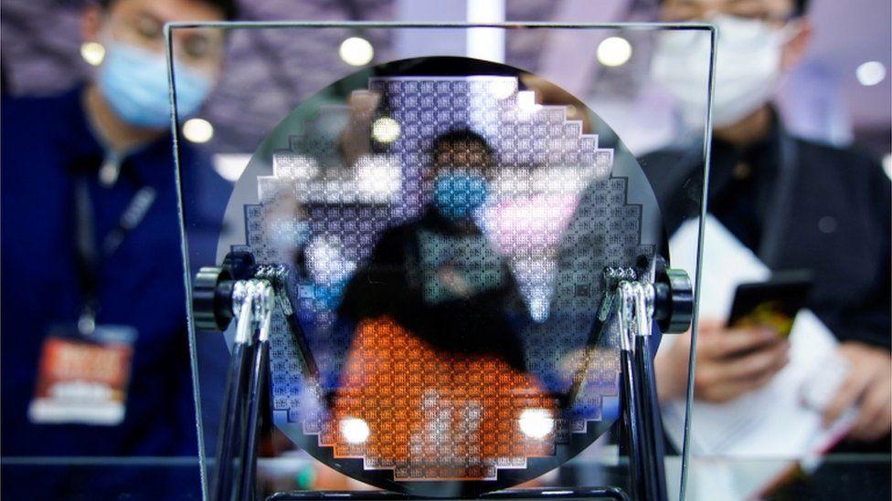 Visitors look at a display of a semiconductor device at Semicon China