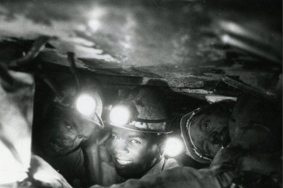 Three of the run men working under the chocks at the coal face at Gedling Colliery