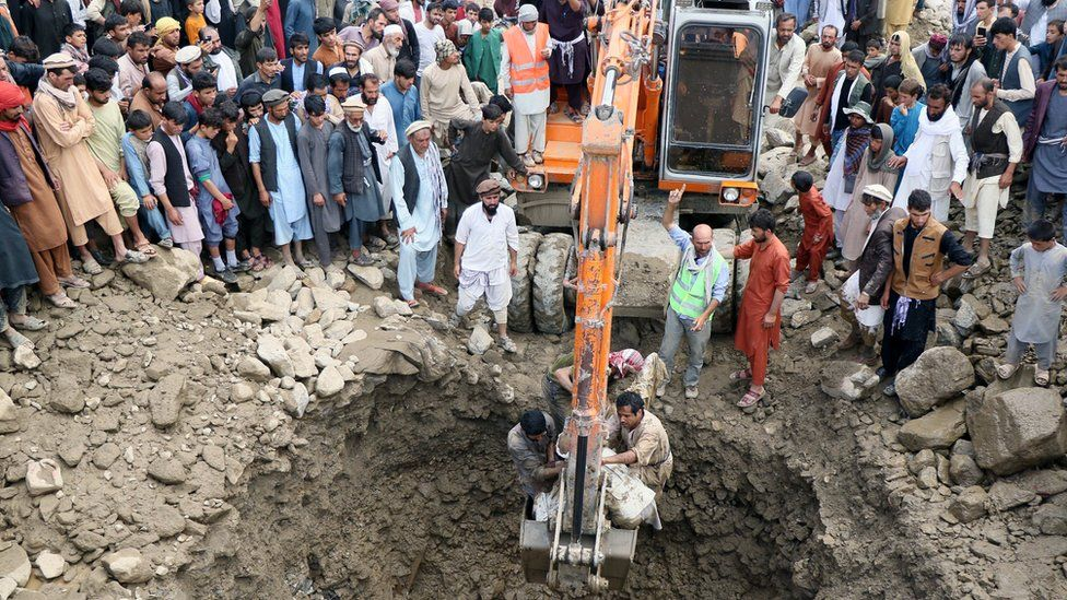 A crane lifts a victim who died in the floods in Charikar