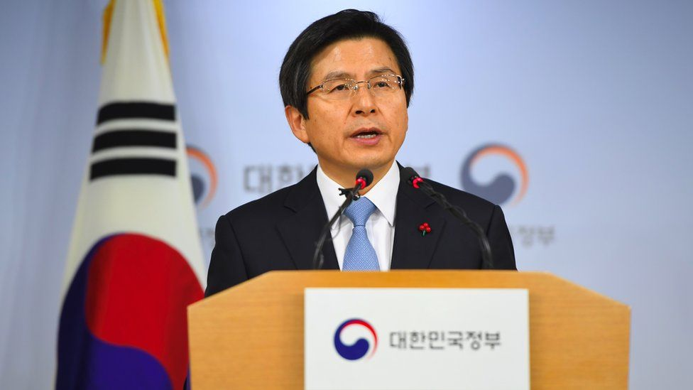 Mr Hwang Kyo-ahn seen speaking at a podium, in front of the South Korean flag