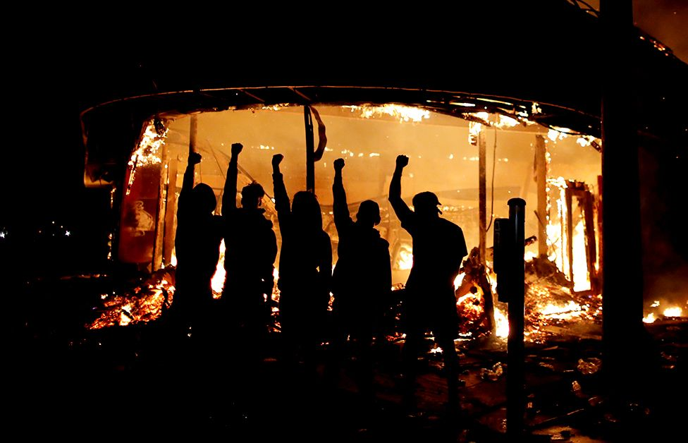Protesters are seen outside of a liquor store on fire