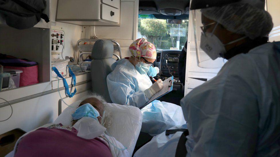A nurse fills in a form on behalf of an elderly patient inside an ambulance in Sao Paulo, Brazil (2 July 2020)
