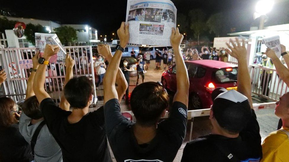 Apple Daily journalists hold freshly-printed copies of the last edition while acknowledging supporters gathered outside their office