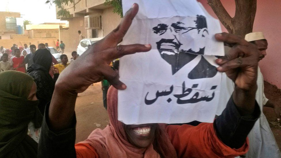 "A Sudanese protester carries a portrait of President Omar al-Bashir with Arabic writing that reads ""Down and that is all"" during an anti-government demonstration east of the capital Khartoum on 9 February 2019"