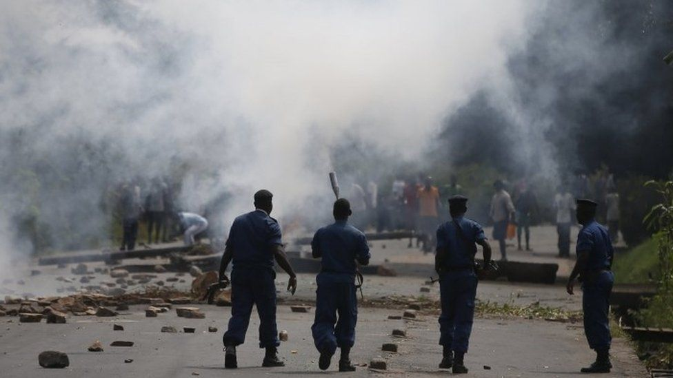 Police in front of tear gas plumes