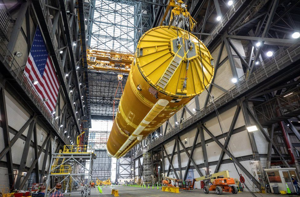 Core stage being lifted up from its position in the transfer aisle at the Vehicle Assembly Building (VAB)