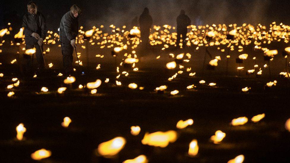 Volunteers light torches in the moat of the Tower of London