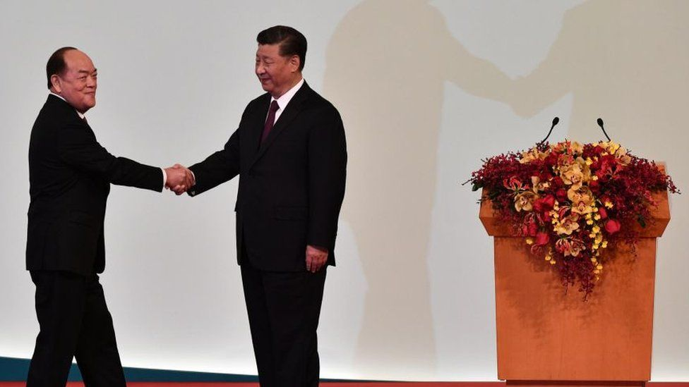 Macau's new chief executive Ho Iat-seng (L) shakes hands with China's President Xi Jinping