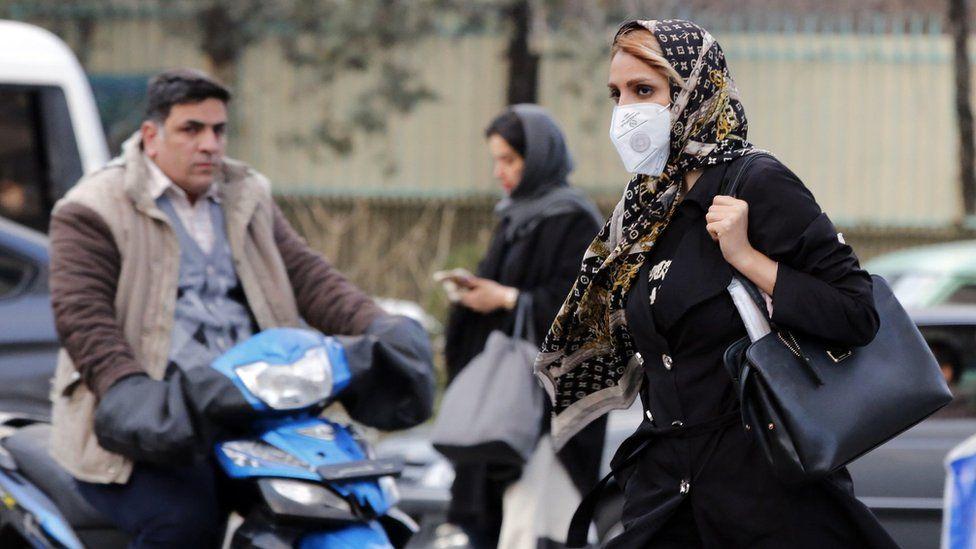 A woman wearing a face mask walks on a street in Tehran, Iran (22 February 2020)