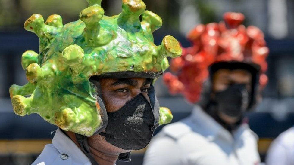 Traffic police personnel wearing coronavirus-themed helmets participate in a campaign to educate the public