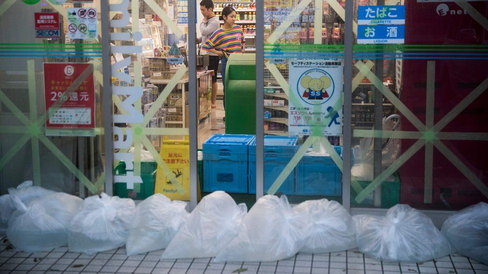 A shop in Tokyo has taped up windows and bags filled with water at its entrance in preparation for Typhoon Hagibis on 12 October.