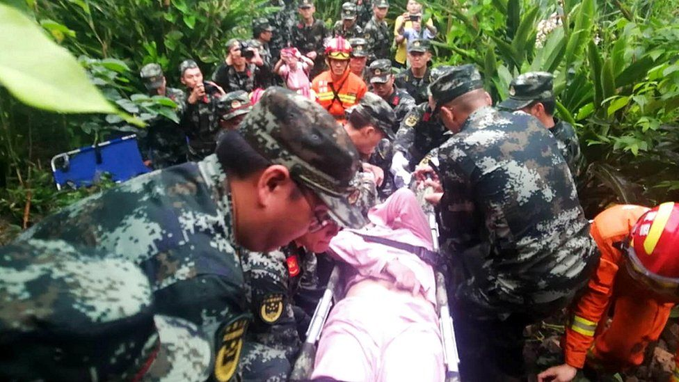 Sichuan police carry an injured person to a medical aid point in Changning county, Yibin city, Sichuan province, 18 June 2019