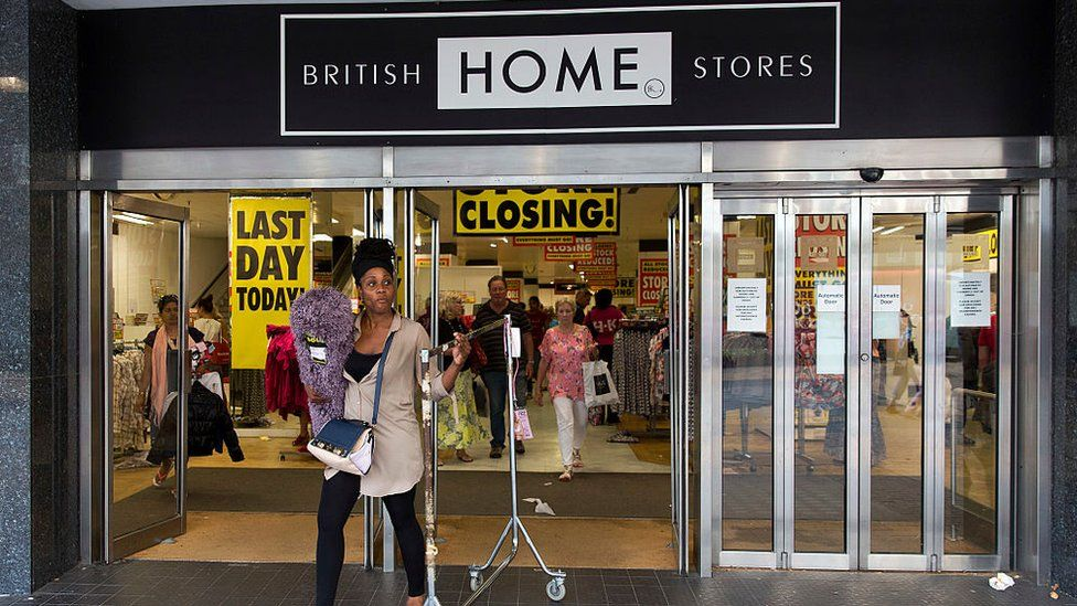A woman buys a clothing rail during the BHS closing down sale in 2016