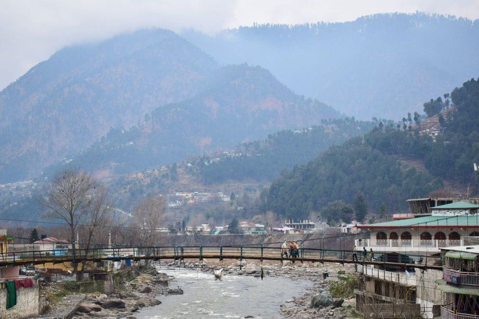 Pakistani residents walk on a bridge in the mountainous area of Balakot where the Indian Air Force launched a a strike on 26 February 2019.