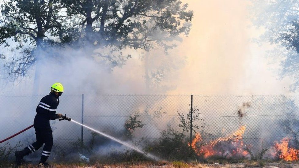A firefighter battles a fire in Artigues, south-eastern France. Photo: 25 July 2017
