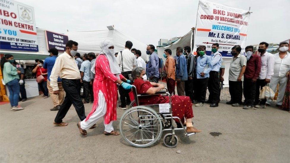 A woman in a wheelchair leaves a vaccination centre after receiving a dose of the coronavirus disease (COVID-19) vaccine during a vaccination drive, in Mumbai, India, April 8, 2021