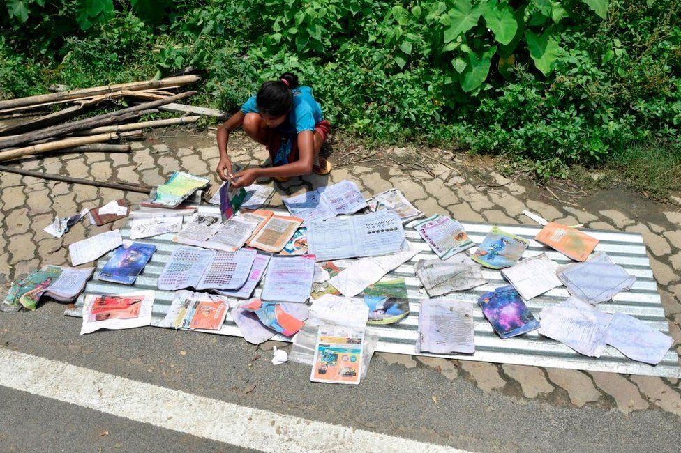 A girl places her school books to dry along a roaside at the flood affected area of Hatishila in Kamrup district of India's Assam state on July 16, 2019.