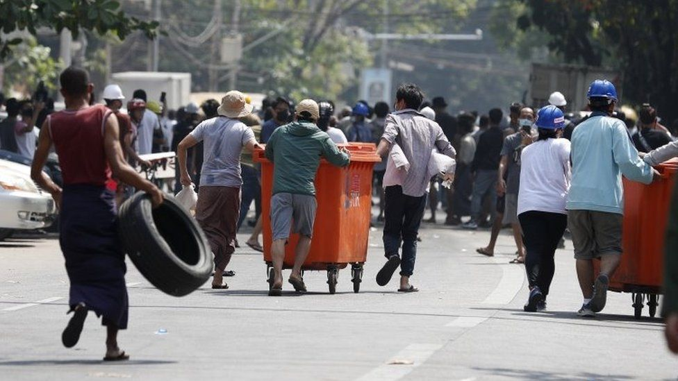 Demonstrators move rubbish bins and tires to build barricades during a protest