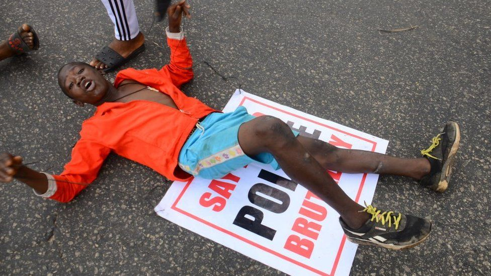 Youths of ENDSARS protesters display their placards in a crowd in support of the ongoing protest against the harassment, killings and brutality of The Nigerian Police Force Unit called Special Anti-Robbery Squad (SARS) at Alawusa bus stop, along Lagos Ibadan-Expressway in Ikeja, on October 13, 2020