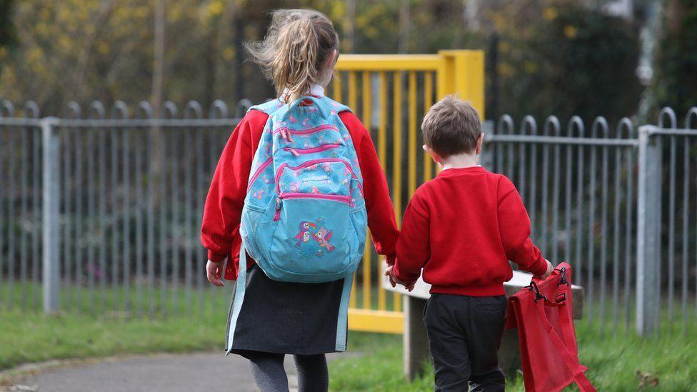 Two school children walking hand-in-hand