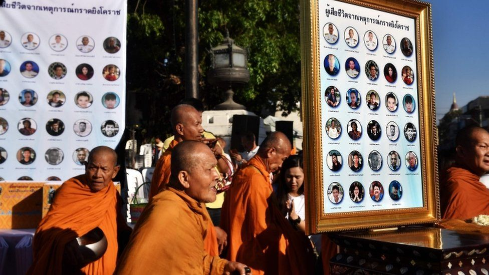 Buddhist monks walk past photographs of the victims of a mass shooting one week after a lone soldier shot and killed 29 people in Thailand
