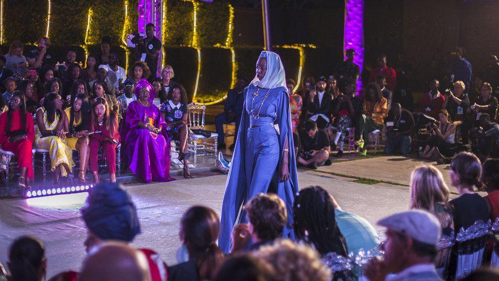 Un mannequin se promène sur un podium en portant un motif de la marque de mode sénégalaise So' Fatoo pendant la Semaine de la mode de Dakar à Dakar, Sénégal.