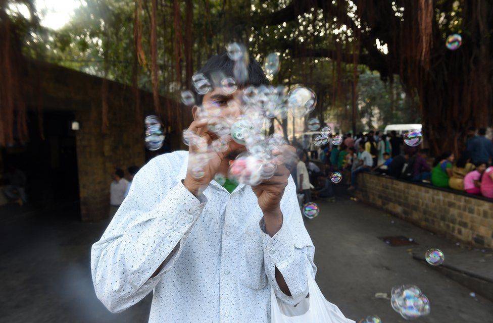 A unemployed young Indian man sells self-made bubble making device