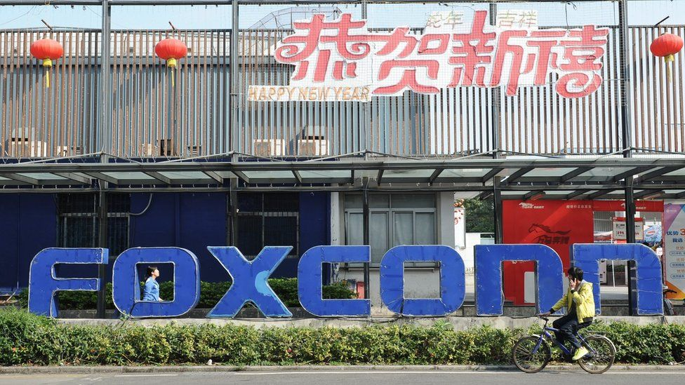 This picture taken on February 22, 2013 shows people walking past a Foxconn recruitment point in Shenzhen, south China's Guangdong province.