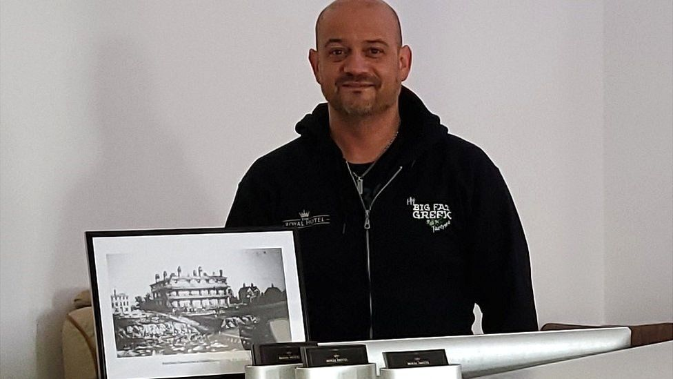 Jason Smedley with a photograph of the hotel